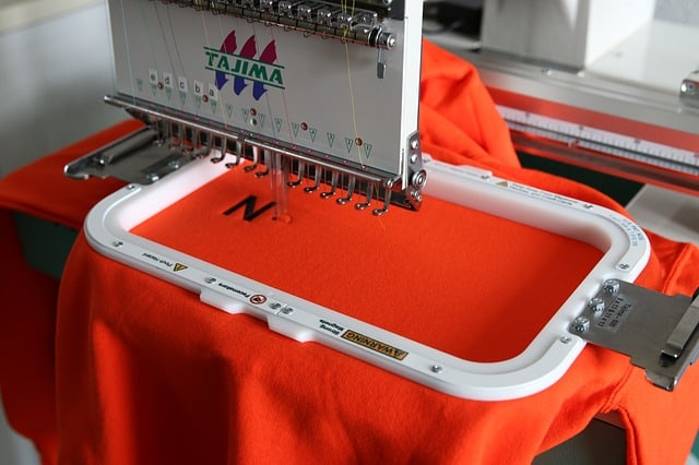 Commercial embroidery machine creating custom t-shirt design