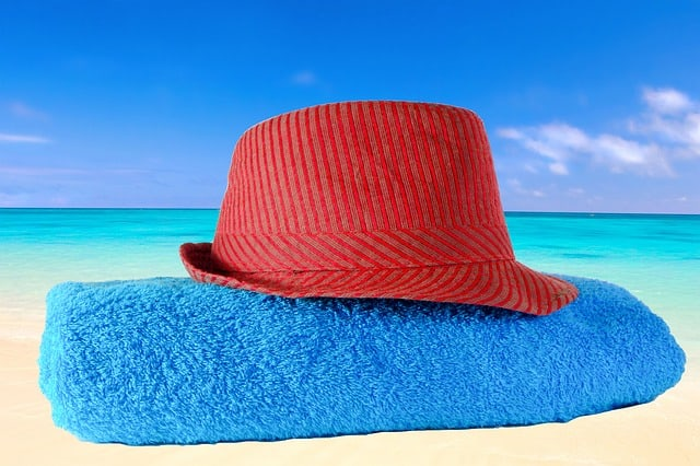 Red hat on folded blue beach towel with an ocean view