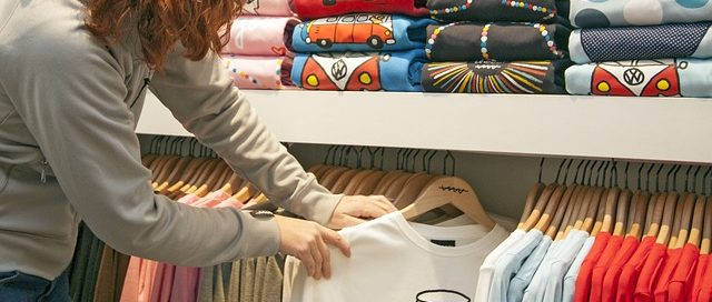 Woman browsing screen printed t-shirts on a rack