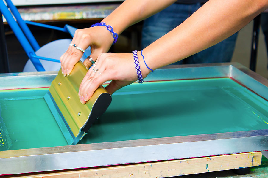 Woman using a screen for screenprinting