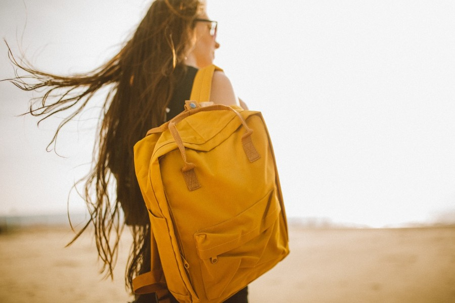 Person carrying yellow backpack with no logo