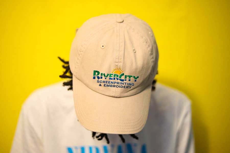 Man wearing a custom embroidered hat with the RCSE logo