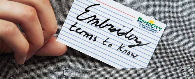 """Man putting a note card into his pocket with the text """"Embroidery terms to know"""" hand-written on the card"""