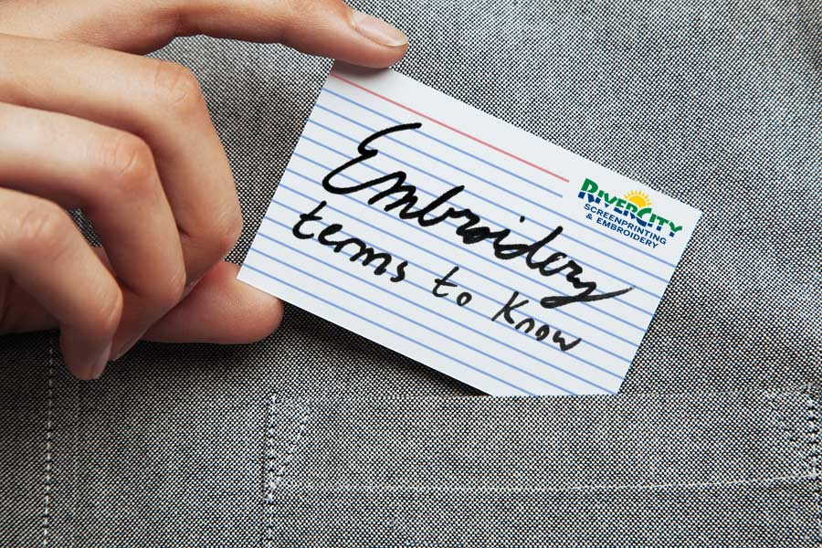 "Man putting a note card into his pocket with the text ""Embroidery terms to know"" hand-written on the card"